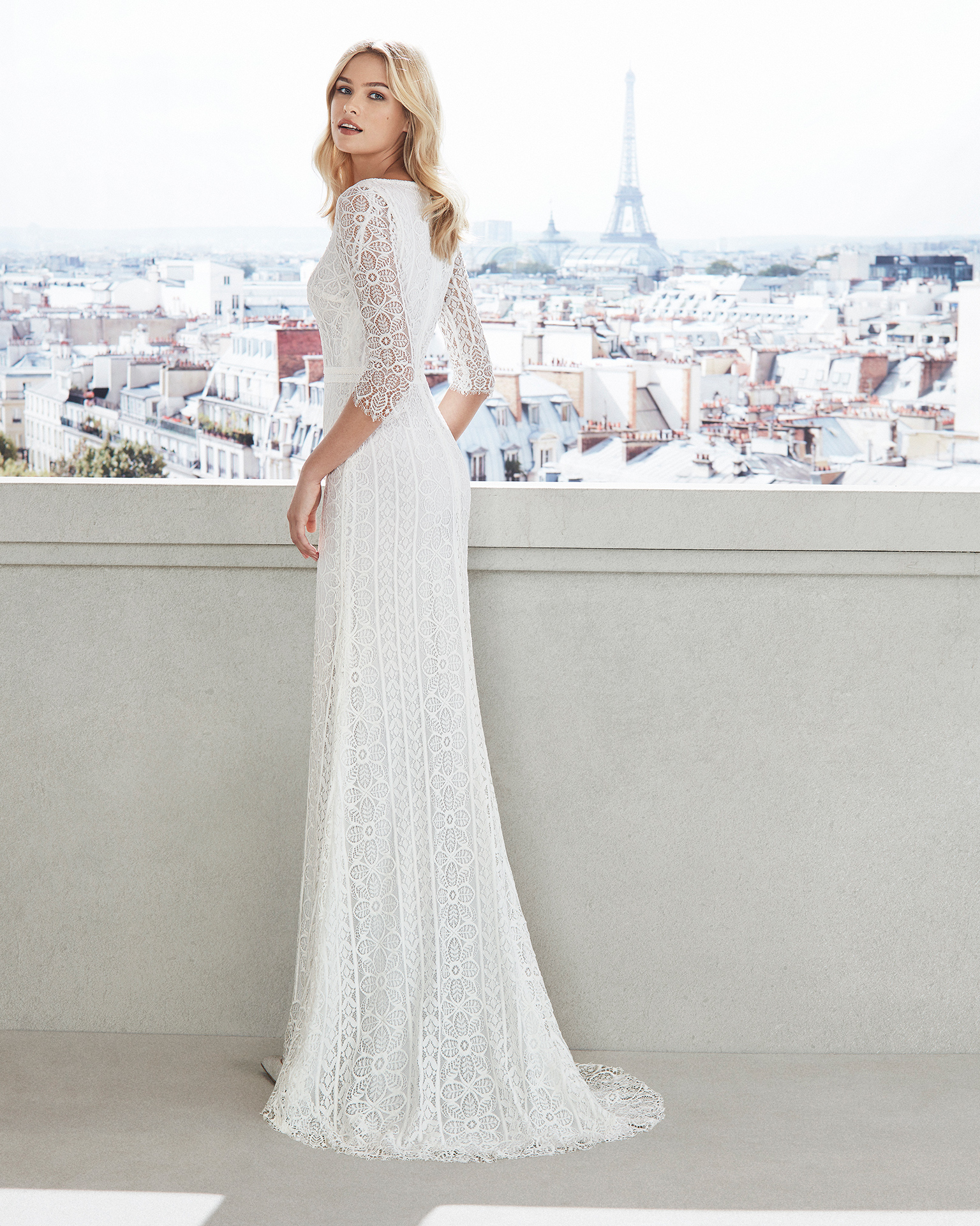 Sheath-style wedding dress in lace. V-neckline, long sleeves and slit skirt. Available in natural. 2019  Collection.