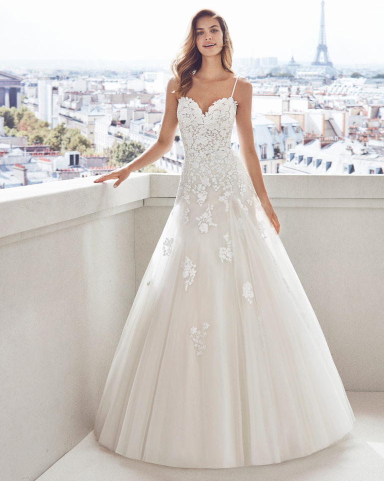 Lace and tulle princess-style wedding dress. Semi-sweetheart neckline, beaded straps and skirt and bodice with lace     appliqués. Available in natural/nude and natural. 2019  Collection.