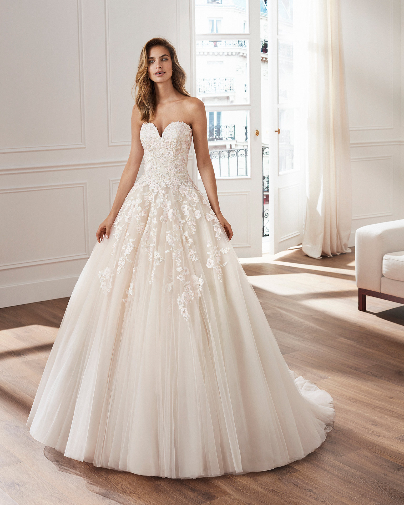 Lace and tulle princess-style wedding dress. Semi-sweetheart neckline and skirt and bodice with lace appliqués. Available in natural/pink and natural. 2019  Collection.
