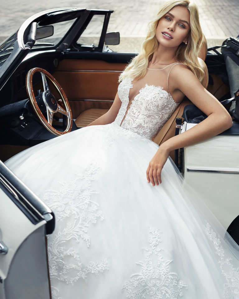 Lace and tulle princess-style wedding dress. Deep-plunge V-neckline with beaded armhole and neckline. Available in      natural. 2019  Collection.