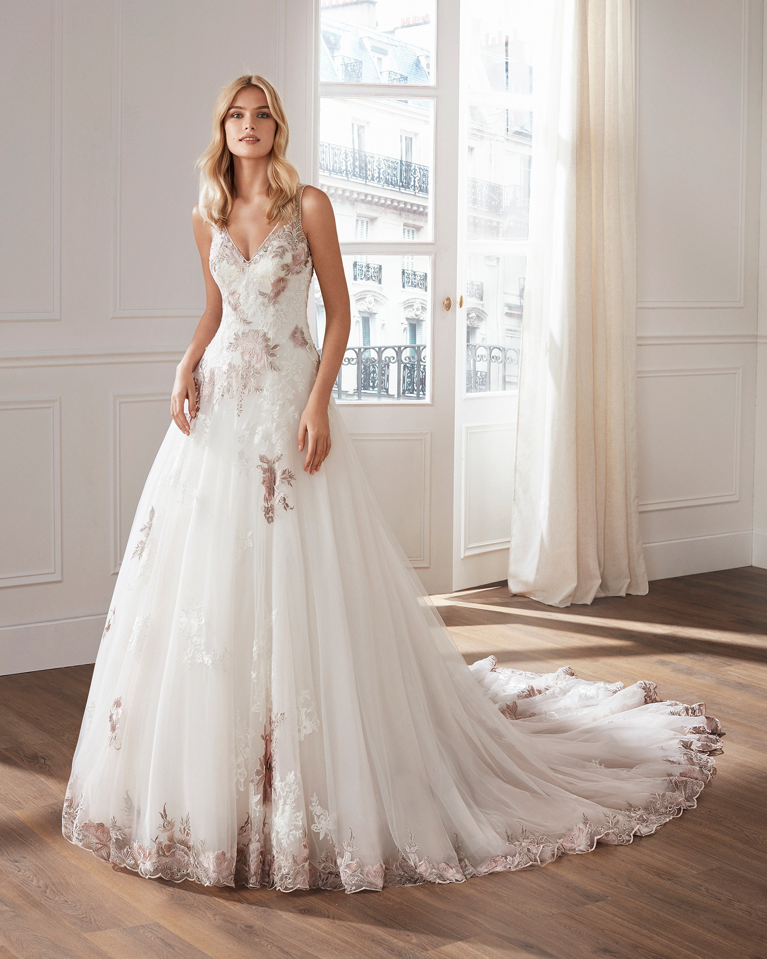 Lace and tulle princess-style wedding dress. V-neckline and skirt and bodice with beaded lace appliqués. Available in natural/pink and natural. 2019  Collection.