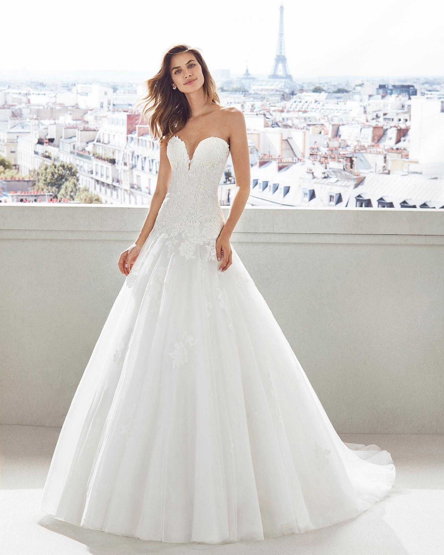 Vestido de novia estilo princesa en tul y encaje. Escote corazón profundo y encaje en cuerpo y falda. Disponible en color natural. Colección  2019.