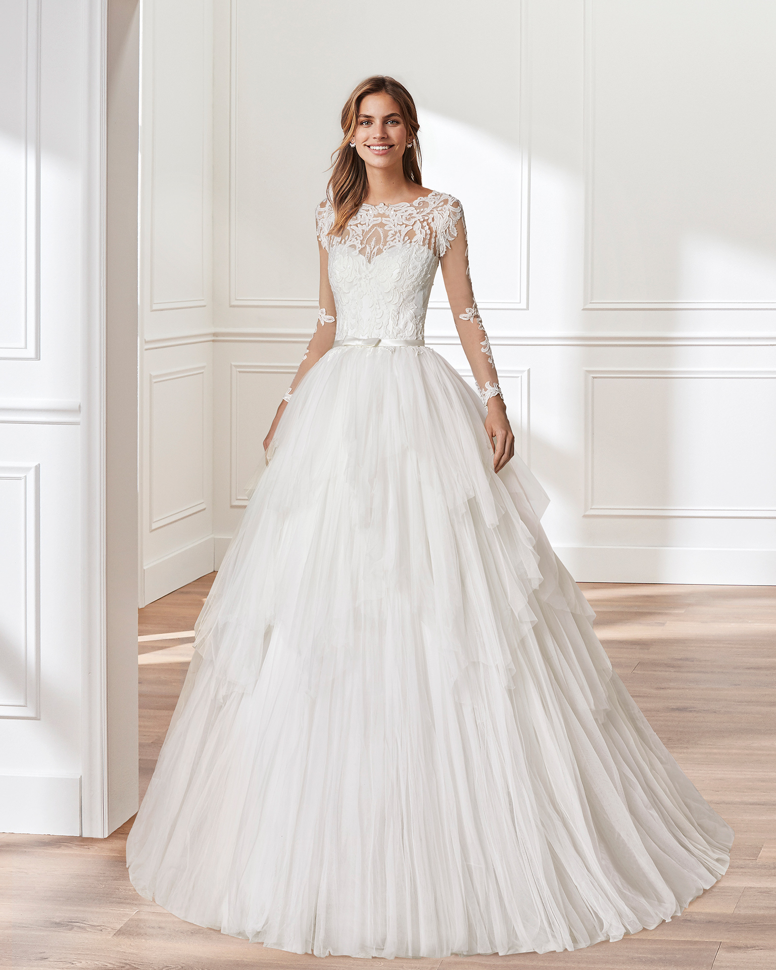 Lace and tulle princess-style wedding dress. Illusion neckline, embroidered bodice of beaded lace and layered tulle skirt. Available in natural. 2019  Collection.