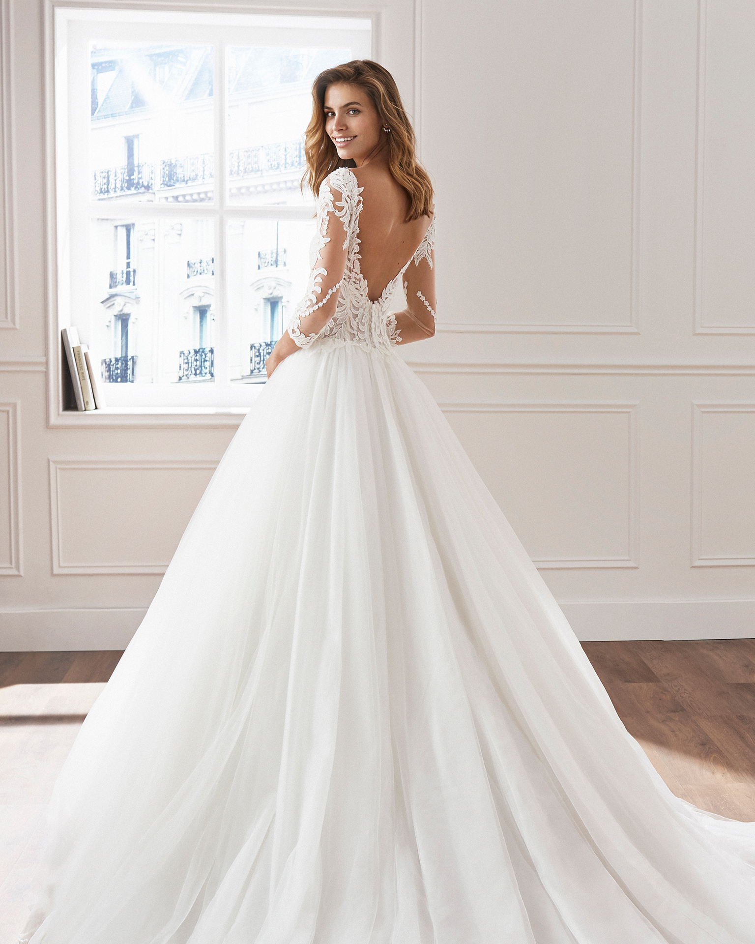 Lace and tulle princess-style wedding dress. Illusion neckline, embroidered bodice of beaded lace and long sleeves. Available in natural. 2019  Collection.