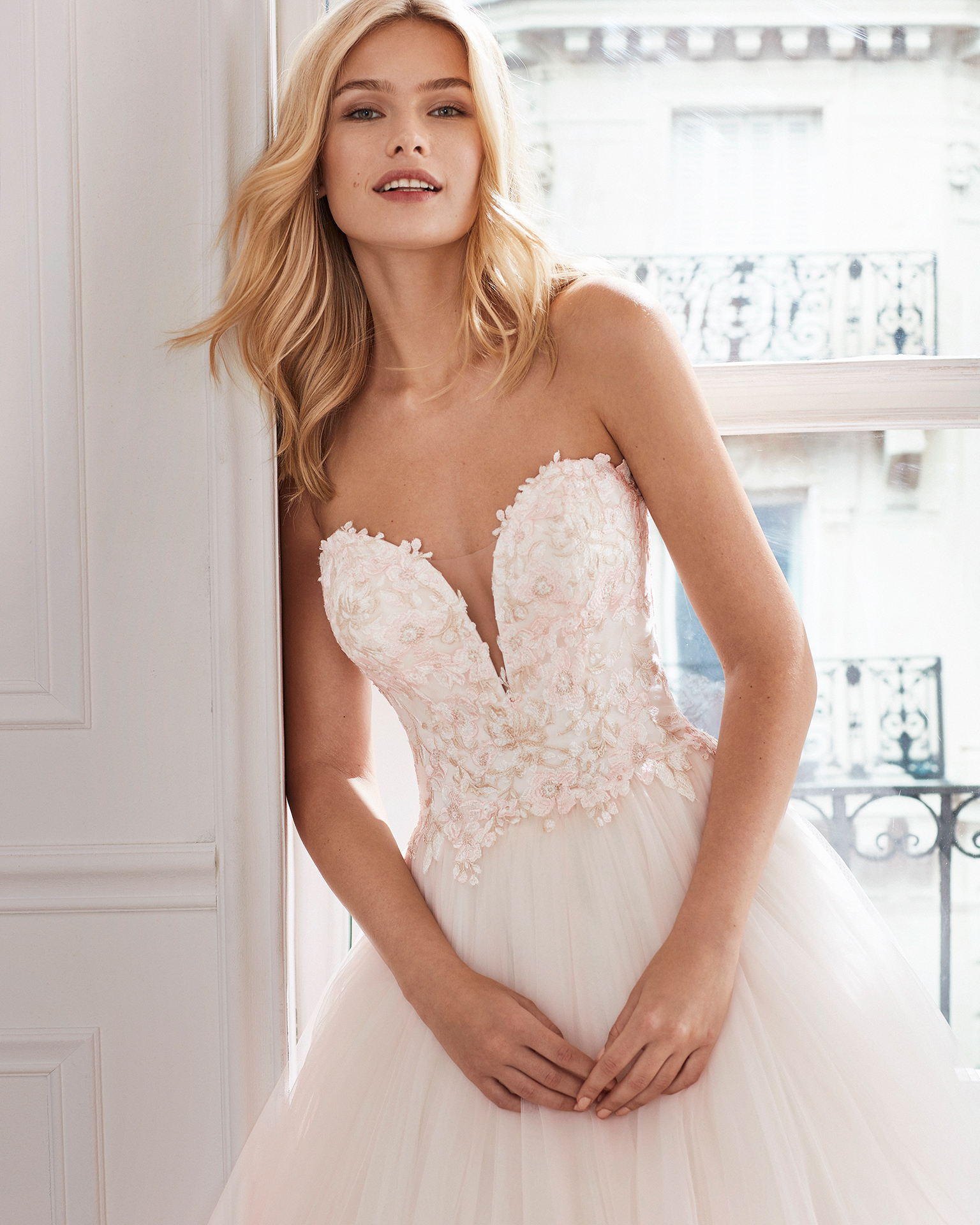 Lace and tulle princess-style wedding dress. Deep-plunge V-neckline and embroidered lace bodice. Available in pink and natural. 2019  Collection.