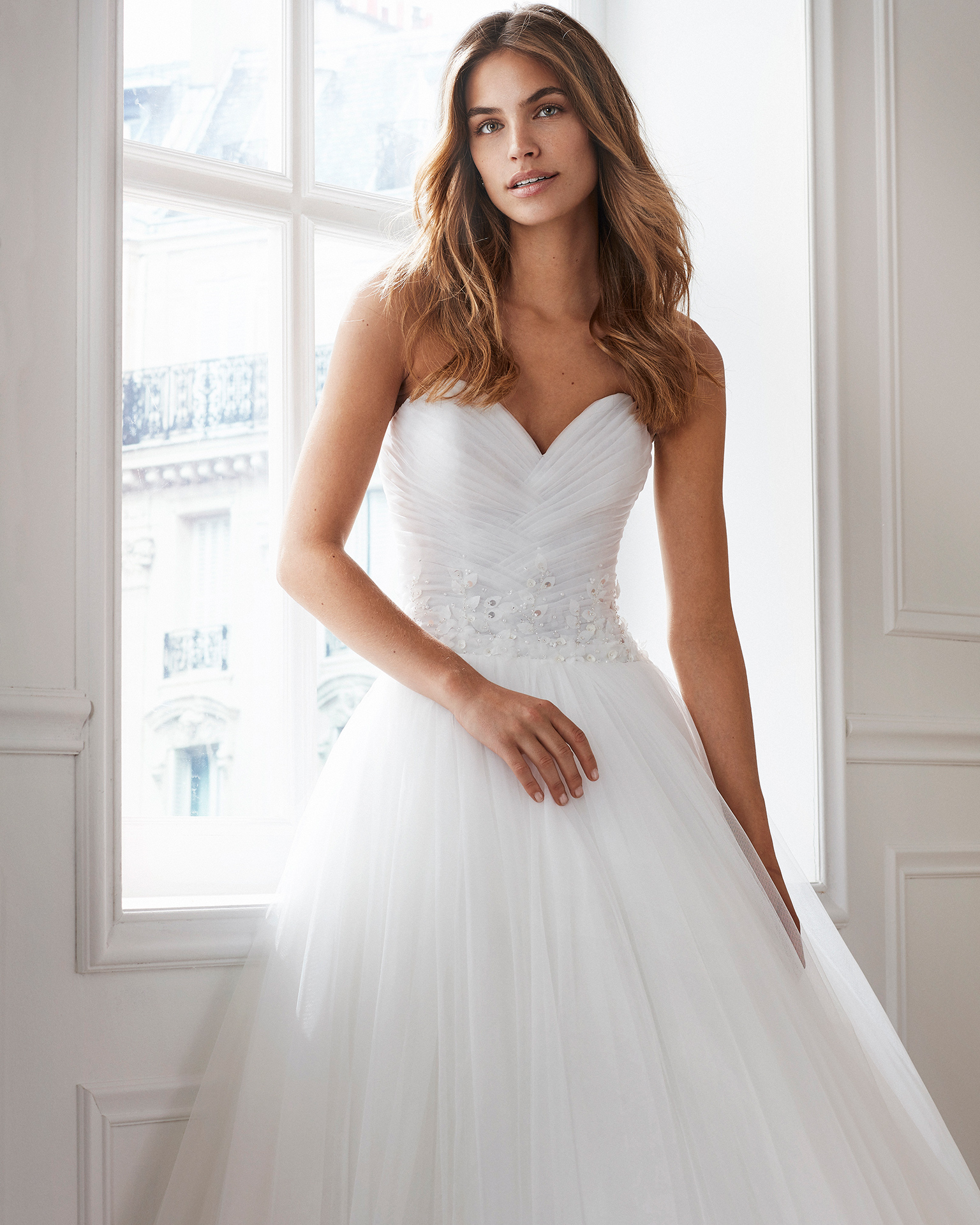 Tulle princess-style wedding dress. Sweetheart neckline and beaded details at the waist. Available in natural. 2019  Collection.