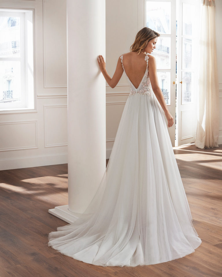 Tulle princess-style wedding dress. V-neckline, draped bodice and appliquéd lace details. Available in natural/pink and natural. 2019  Collection.