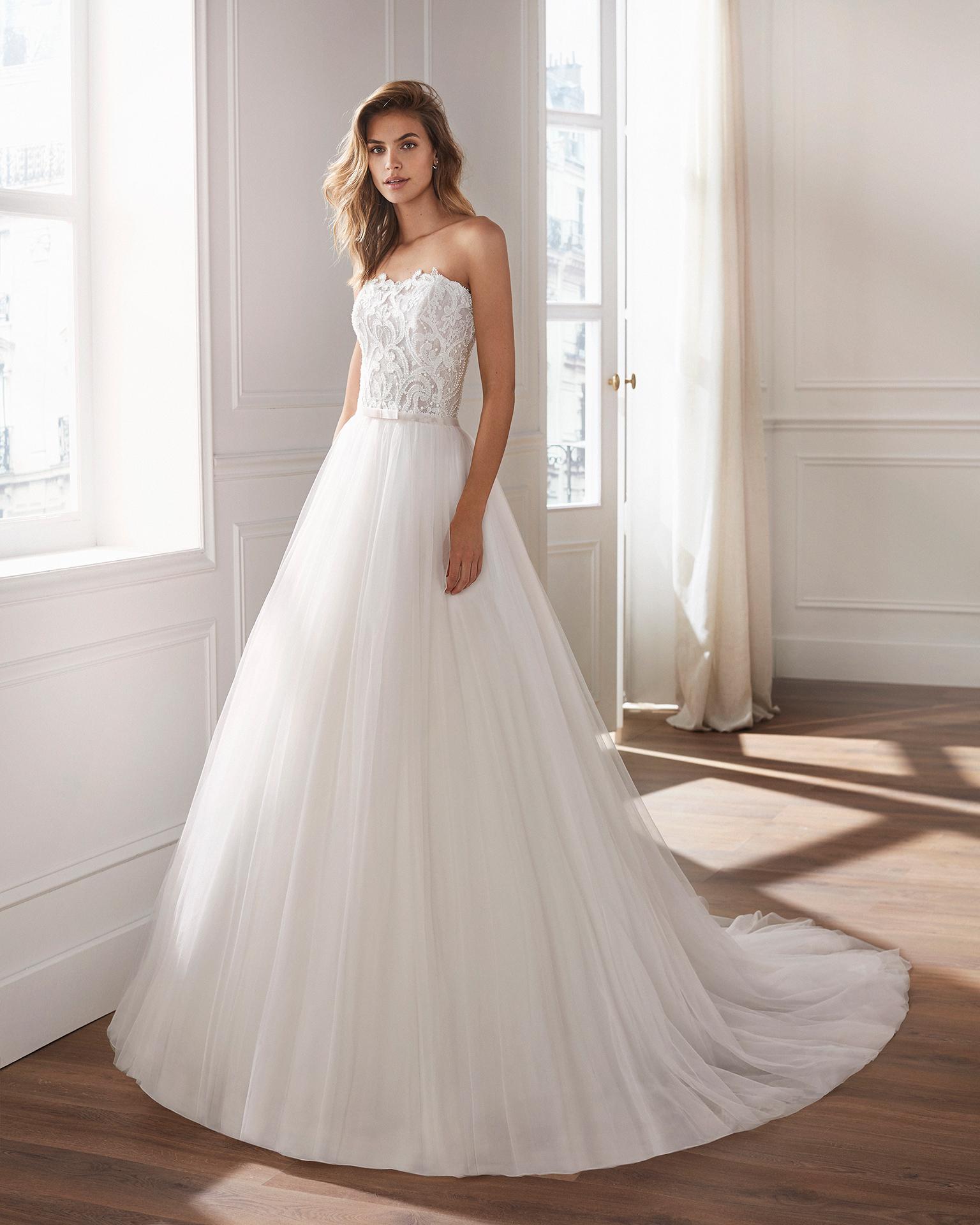 Lace and tulle princess-style wedding dress. Strapless neckline and embroidered bodice of beaded lace. Available in pink and natural. 2019  Collection.