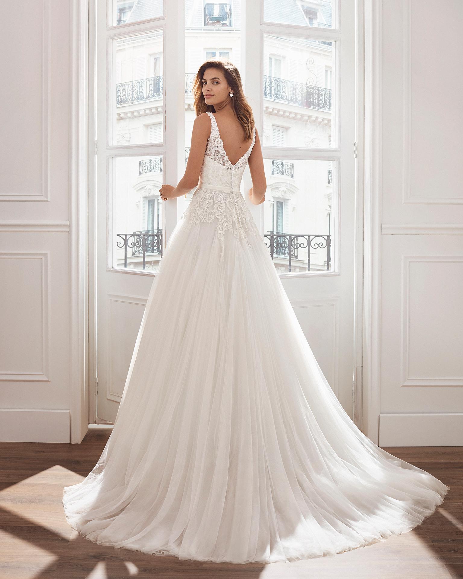 Vestido de novia estilo princesa en tul. Escote en V y cuerpo de encaje pedrería . Disponible en color natural. Colección  2019.