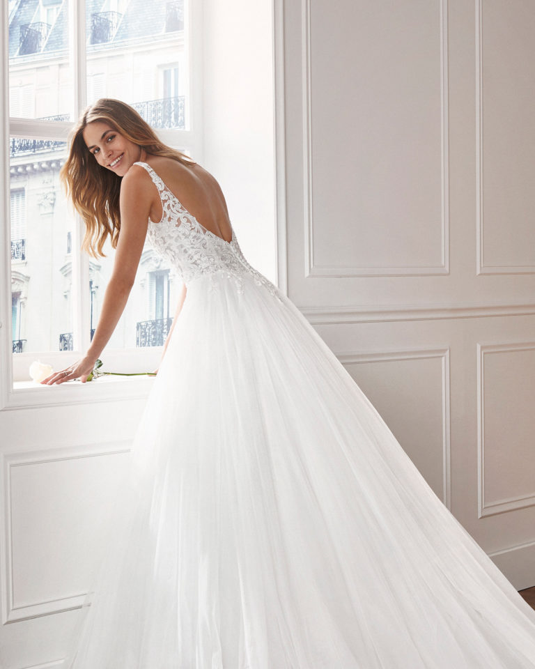 Tulle princess-style wedding dress. V-neckline and lace bodice with open, beaded back. Available in natural. 2019  Collection.