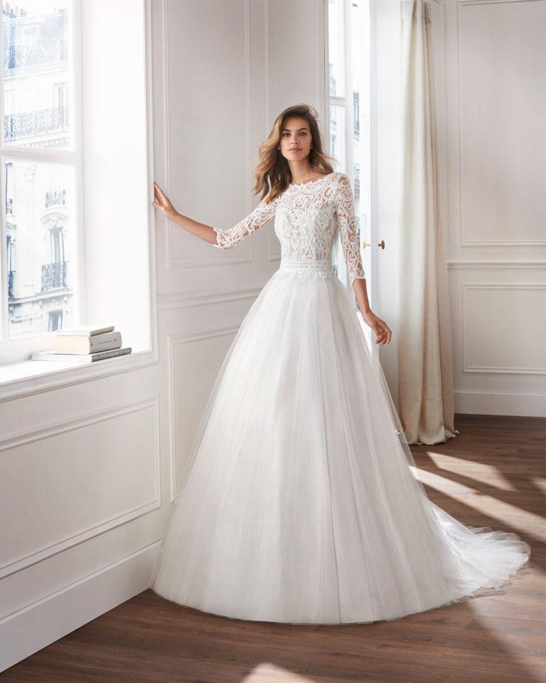 Vestido de novia estilo princesa en tul. Escote ilusión, cuerpo de encaje pedrería y manga larga. Disponible en color natural. Colección  2019.