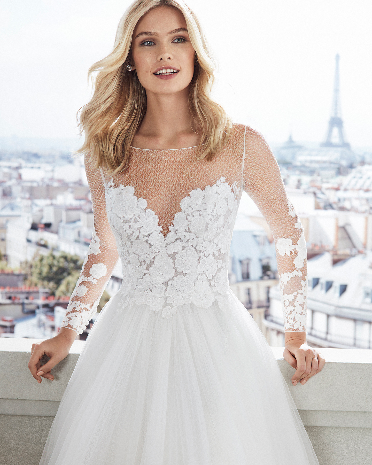 Dot tulle princess-style wedding dress. Illusion neckline, lace bodice and long sleeves. Available in natural. 2019  Collection.