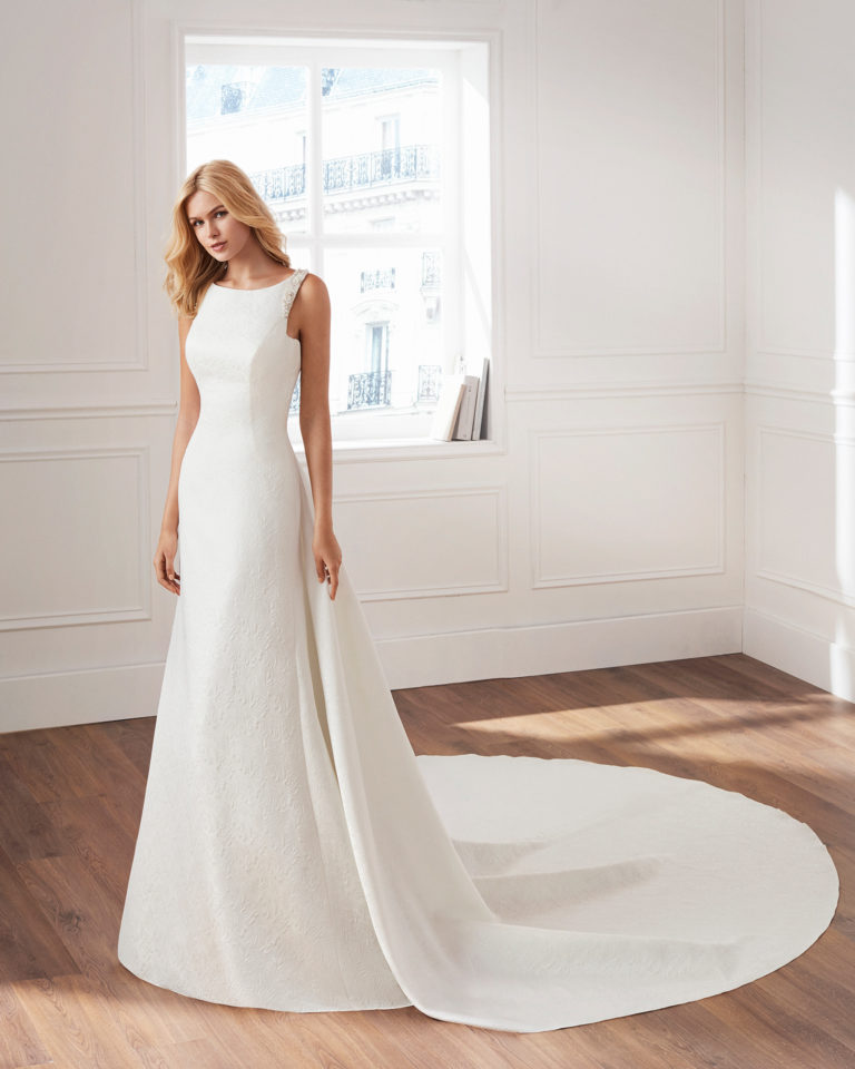 Classic-style brocade wedding dress Bateau neckline, beaded details and removable train. Available in natural. 2019  Collection.