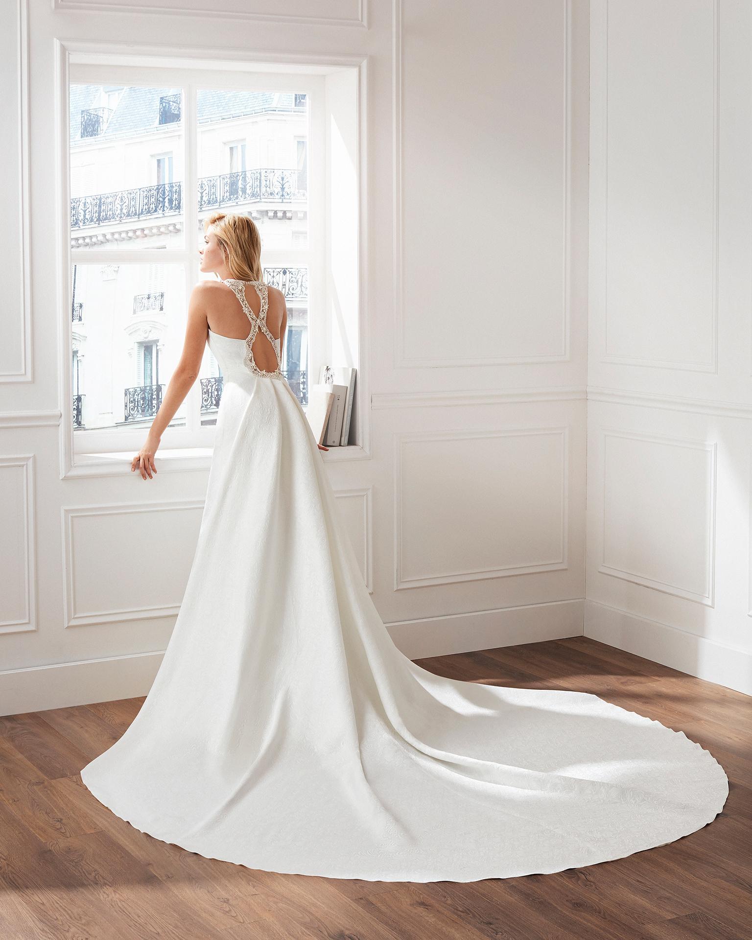 Vestido de novia estilo clásico en brocado. Escote barco, detalles de pedrería y cola desmontable. Disponible en color natural. Colección  2019.