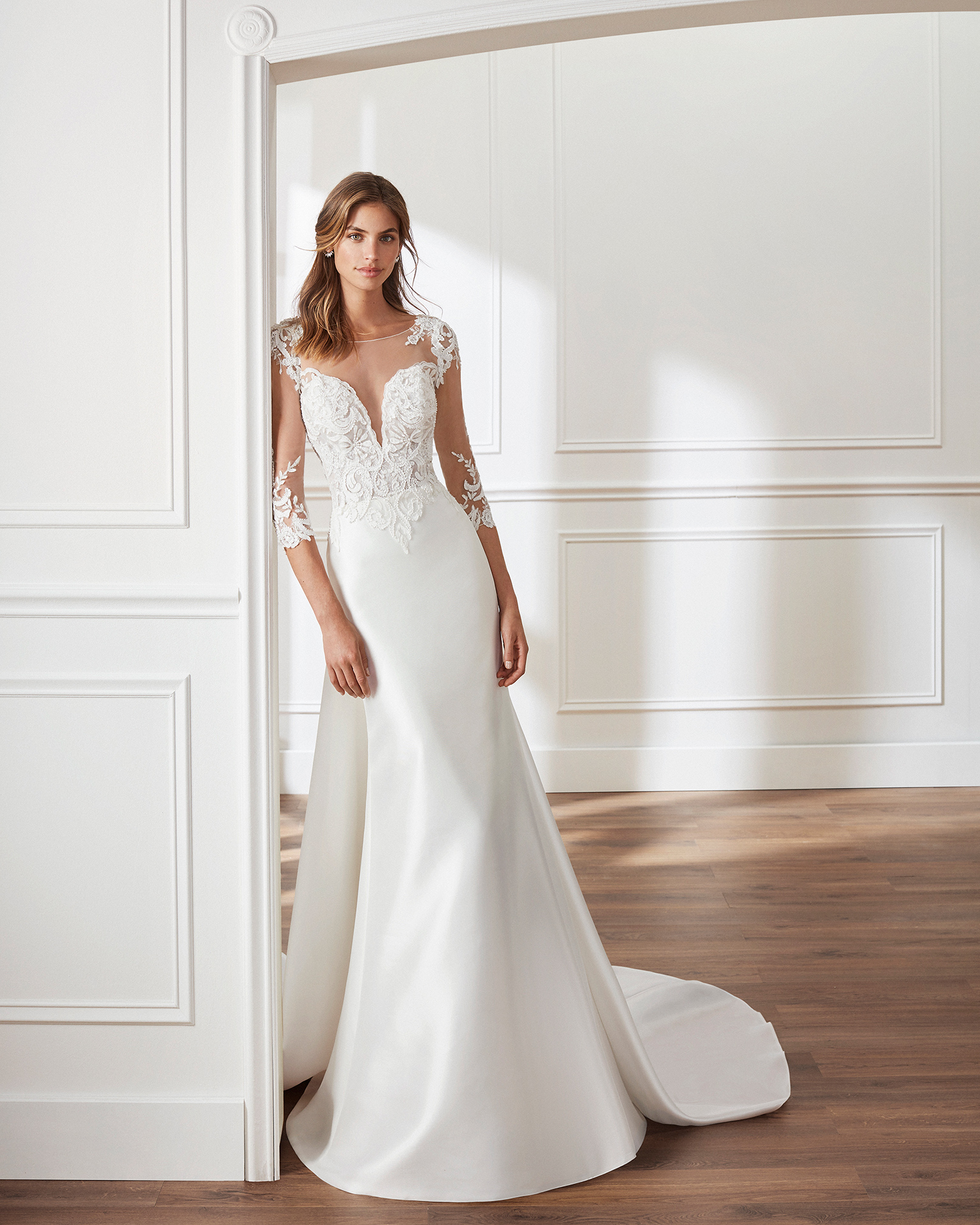 Classic-style mikado wedding dress Deep-plunge V-neckline, long sleeves, beaded lace bodice and removable train. Available in natural. 2019  Collection.