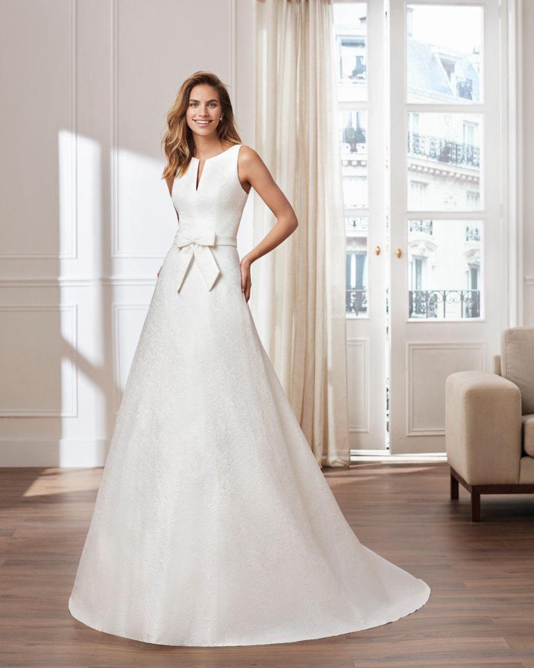 Vestido de novia estilo clásico línea A en brocado. Escote en V en cuerpo y en espalda. Disponible en color natural. Colección  2019.