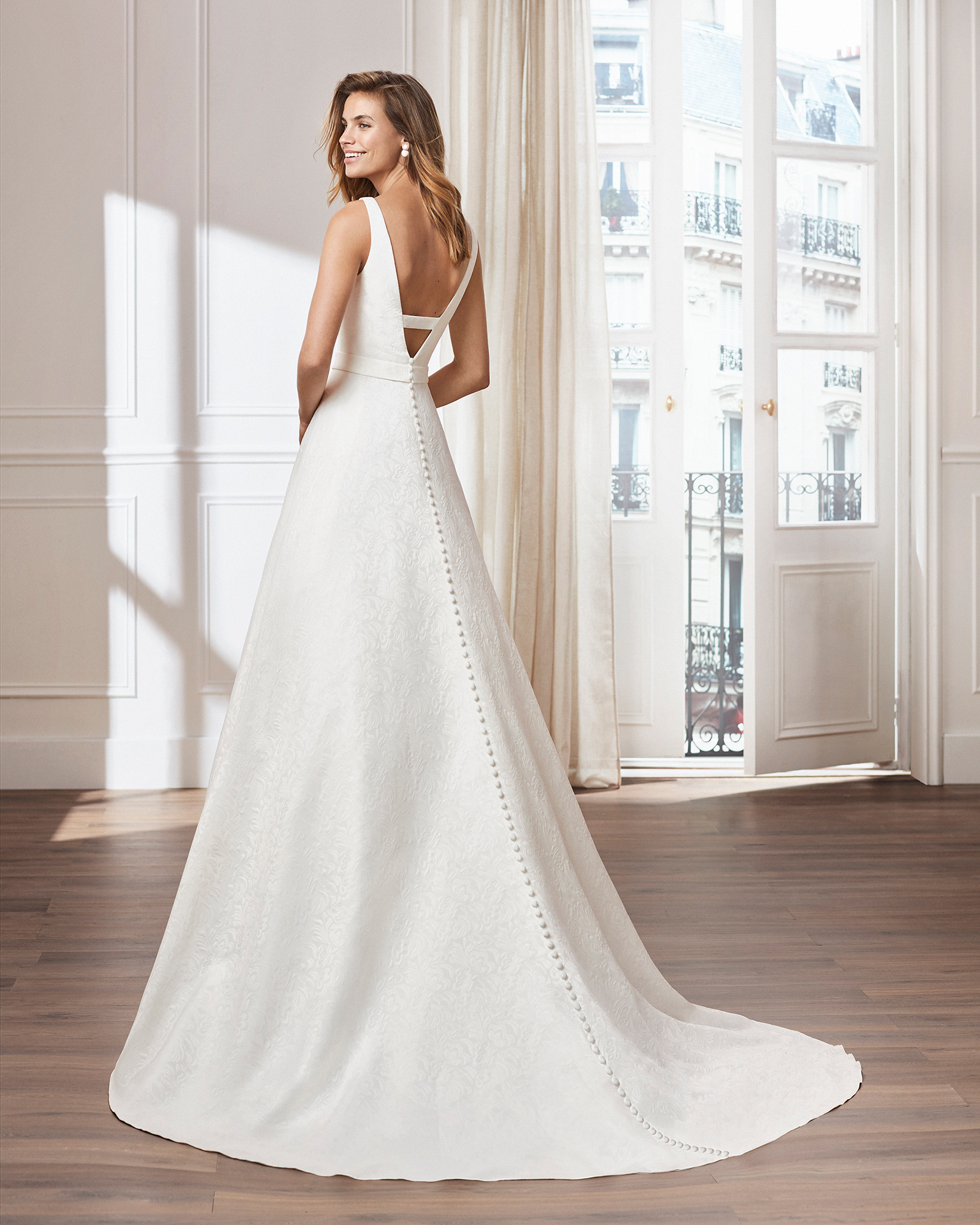 Classic A-line brocade wedding dress. Bodice with front and back V-necklines. Available in natural. 2019  Collection.