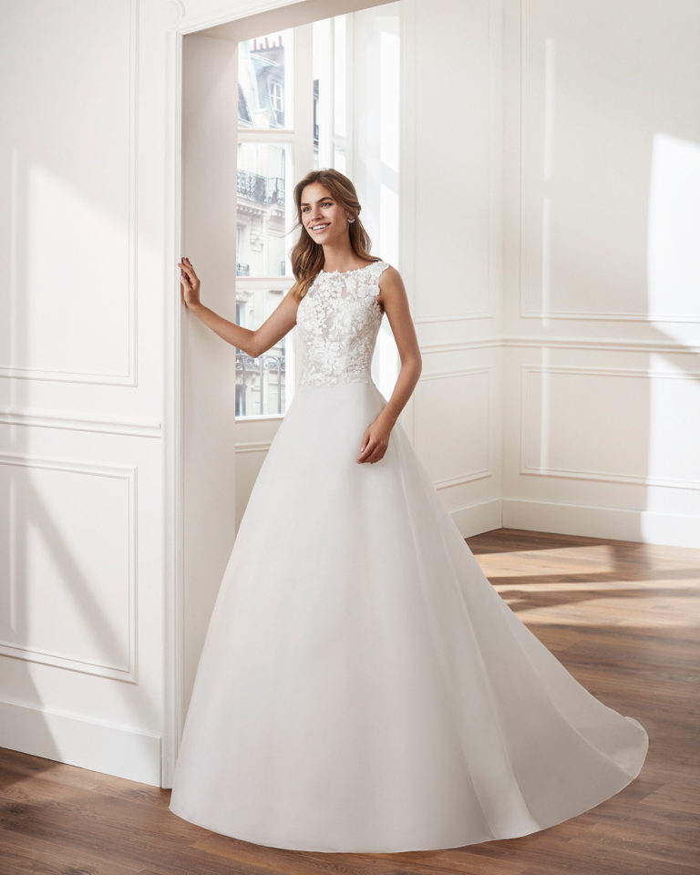 Vestido de novia estilo clásico línea A en gazar. Escote barco y cuerpo de encaje. Disponible en color natural. Colección  2019.