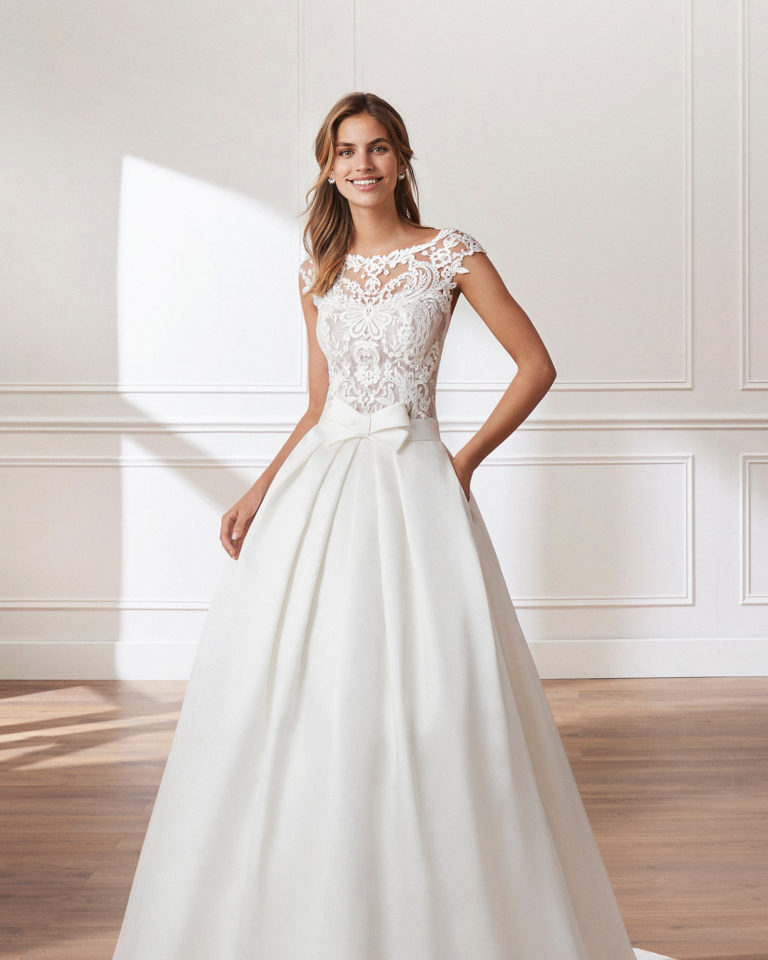 Classic A-line mikado wedding dress. Beaded lace bodice with bateau neckline, short sleeves and pleats at the waist. Available in natural. 2019  Collection.