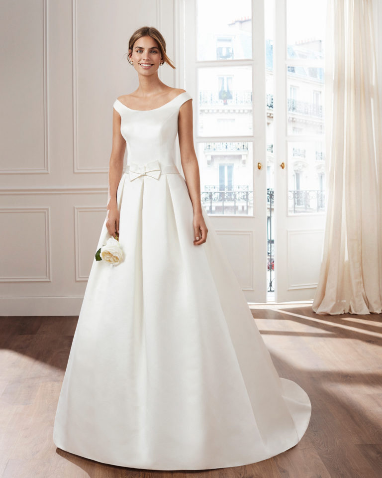 Classic A-line duchess satin wedding dress. Bateau neckline and beaded brooches on the back. Available in ivory. 2019  Collection.