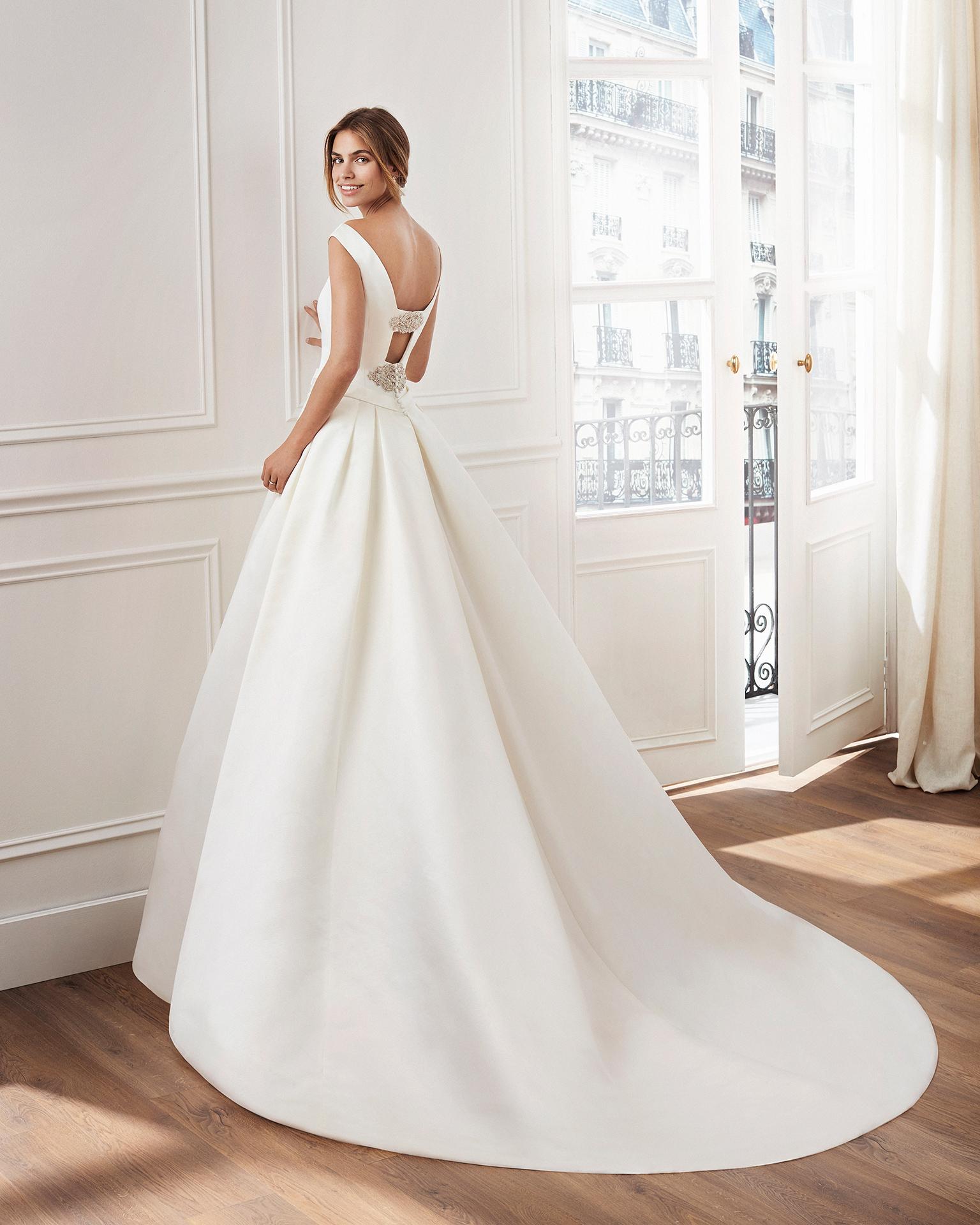 Vestido de novia estilo clásico línea A en raso duquesa. Escote barco y broches de pedrería en espalda. Disponible en color marfil. Colección  2019.