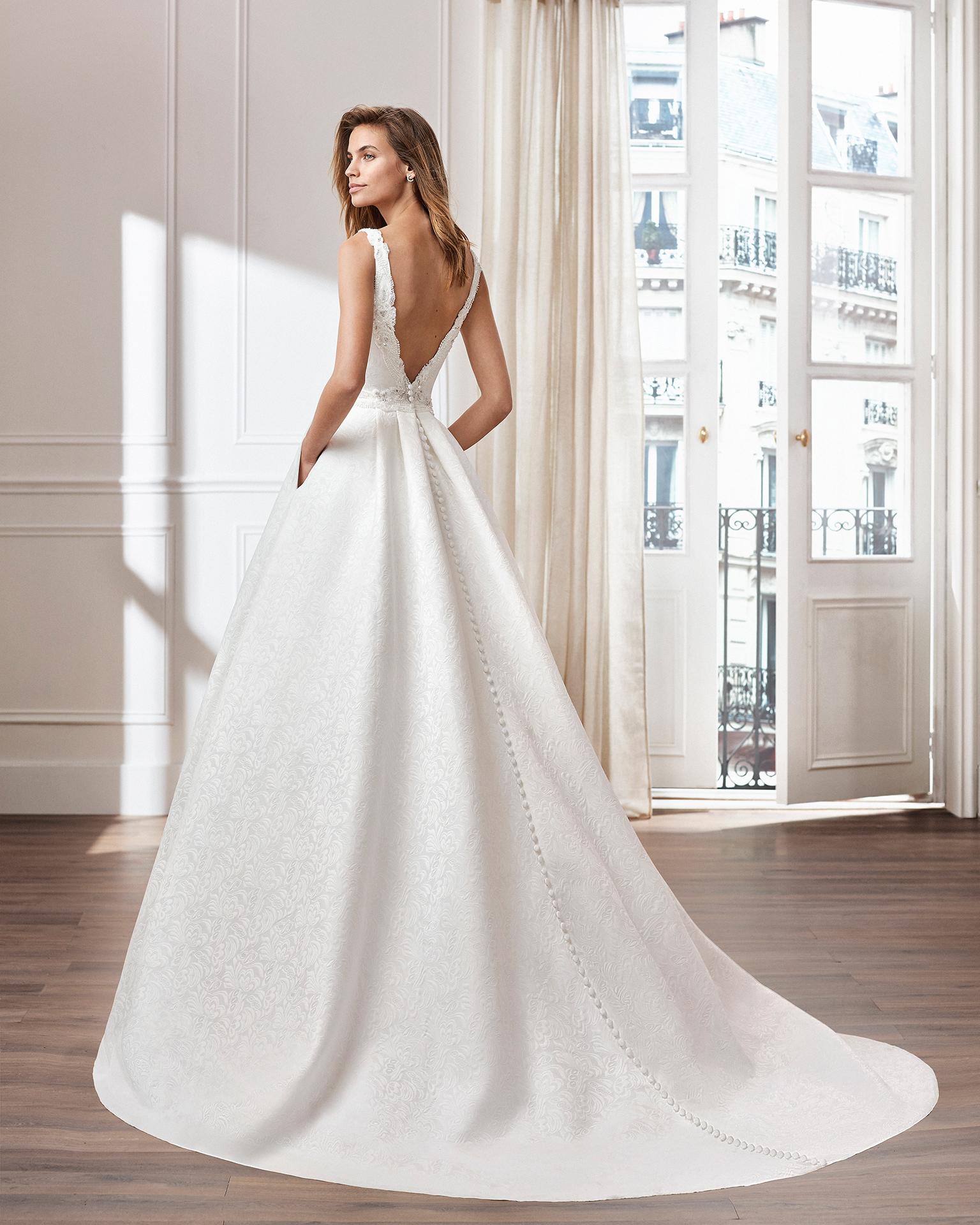 Vestido de novia estilo clásico línea A en brocado. Escote barco y espalda joya. Disponible en color natural. Colección  2019.