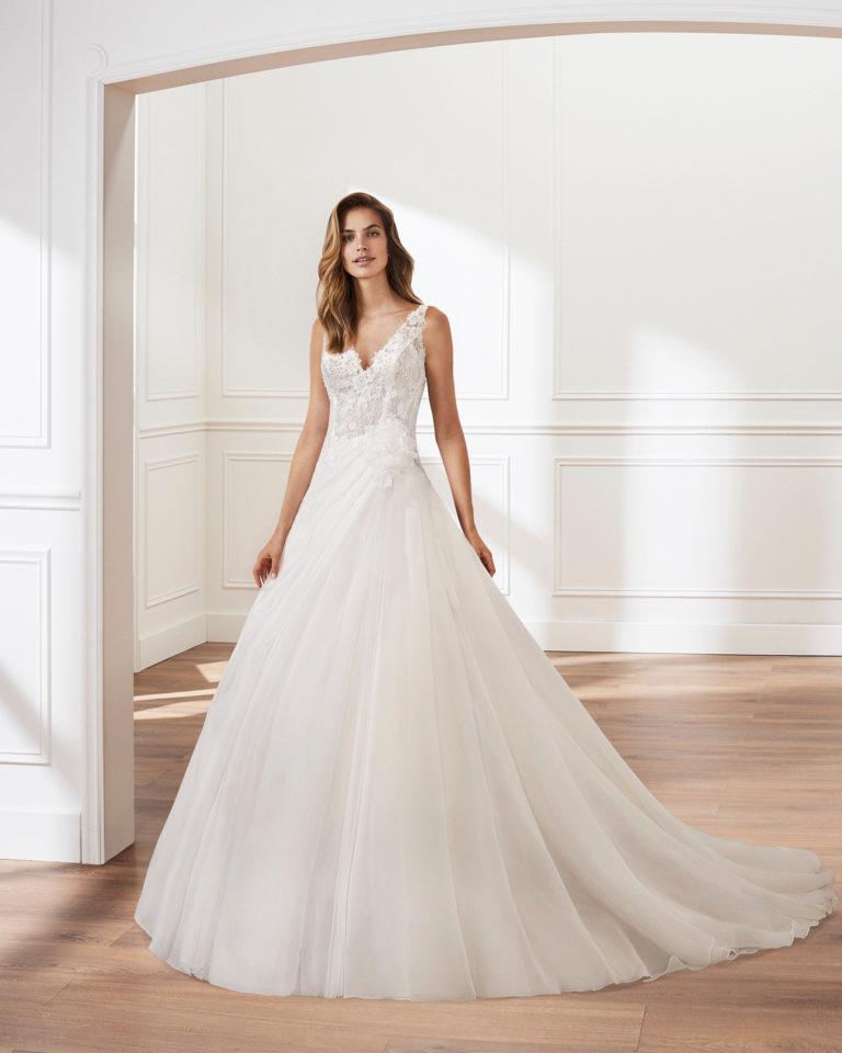 Vestido de novia corte linea A en garza. Escote en V, cuerpo de encaje y falda de pliegues. Disponible en color natural. Colección  2019.