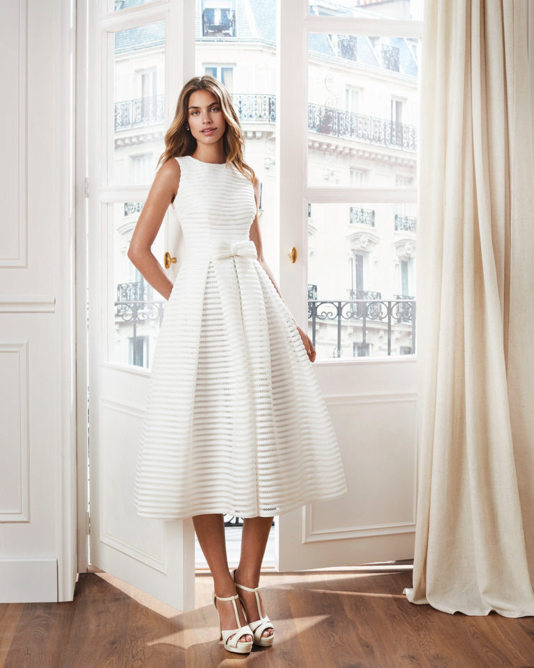 Classic-style short wedding dress. Bateau neckline, V-back and pleated skirt. Available in natural. 2019  Collection.