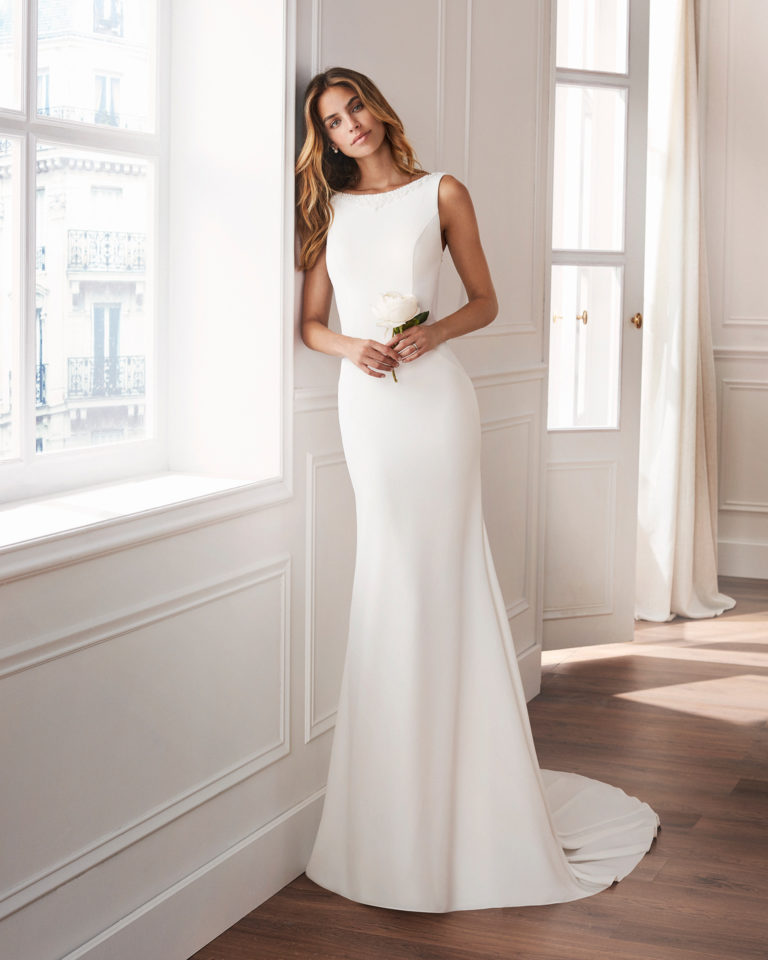 Sheath-style wedding dress in crepe. With bateau neckline, train and jewelled back. Available in natural. 2019  Collection.