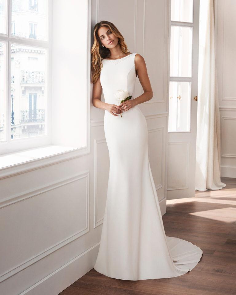 Vestido de novia corte recto en crepe. Con escote barco, arrastre y espalda joya. Disponible en color natural. Colección  2019.