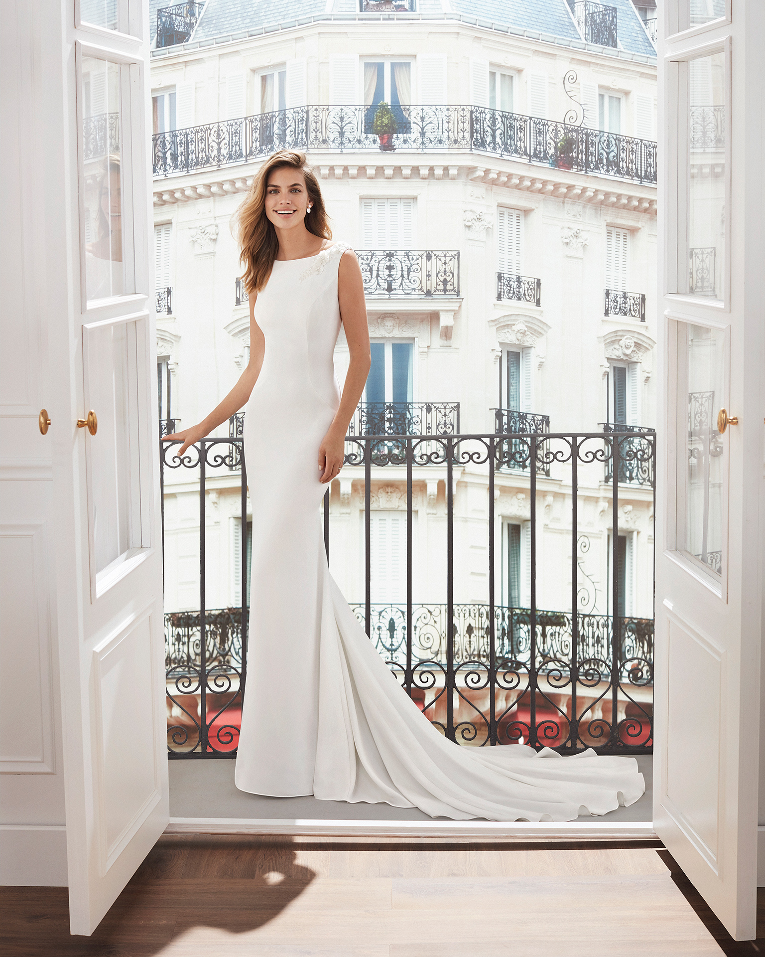 Sheath-style wedding dress in crepe. Sleeveless, with bateau neckline, train and jewelled back. Available in natural. 2019  Collection.
