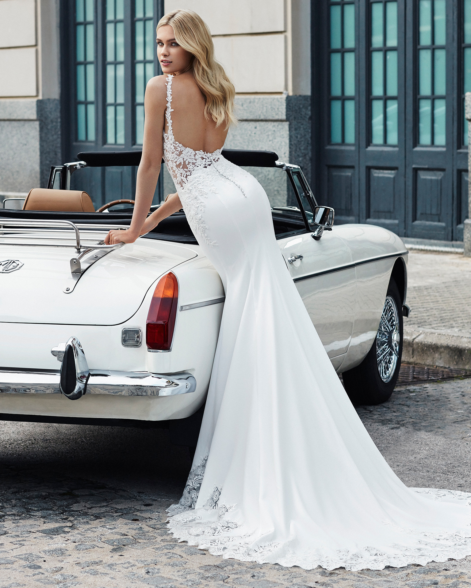 Sheath-style wedding dress in crepe. Sleeveless, V-neckline, beaded lace bodice and train edged with lace. Available in natural. 2019  Collection.