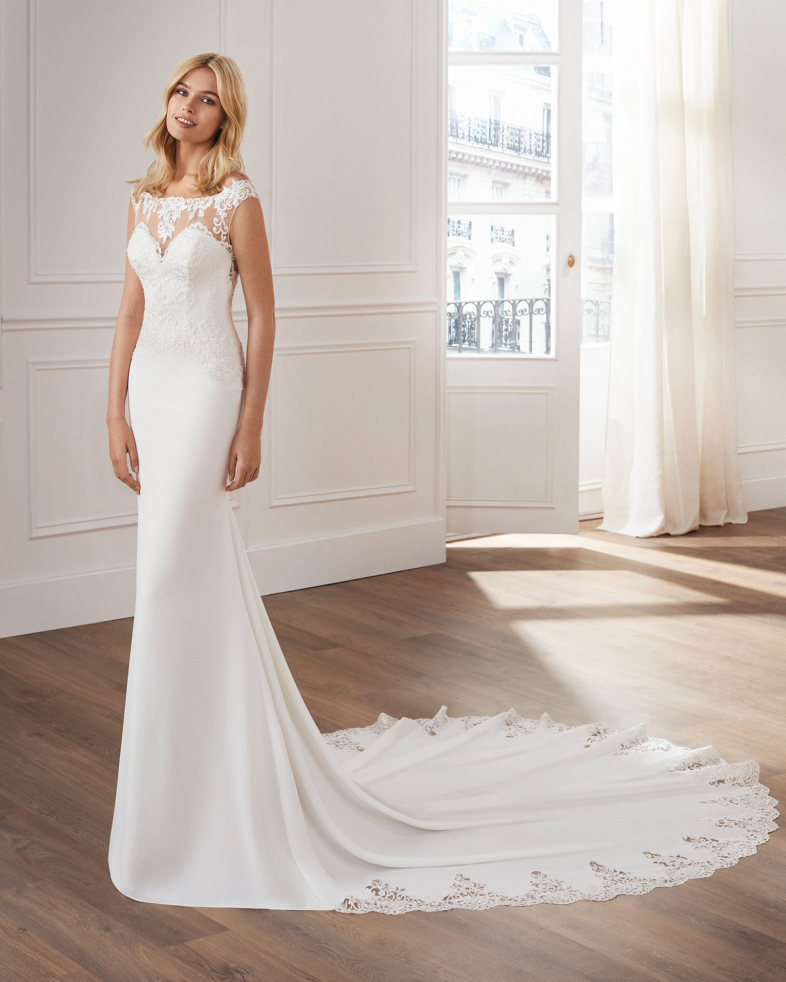 Sheath-style wedding dress in crepe. Sleeveless beaded lace bodice with illusion neckline and train edged with lace. Available in natural. 2019  Collection.