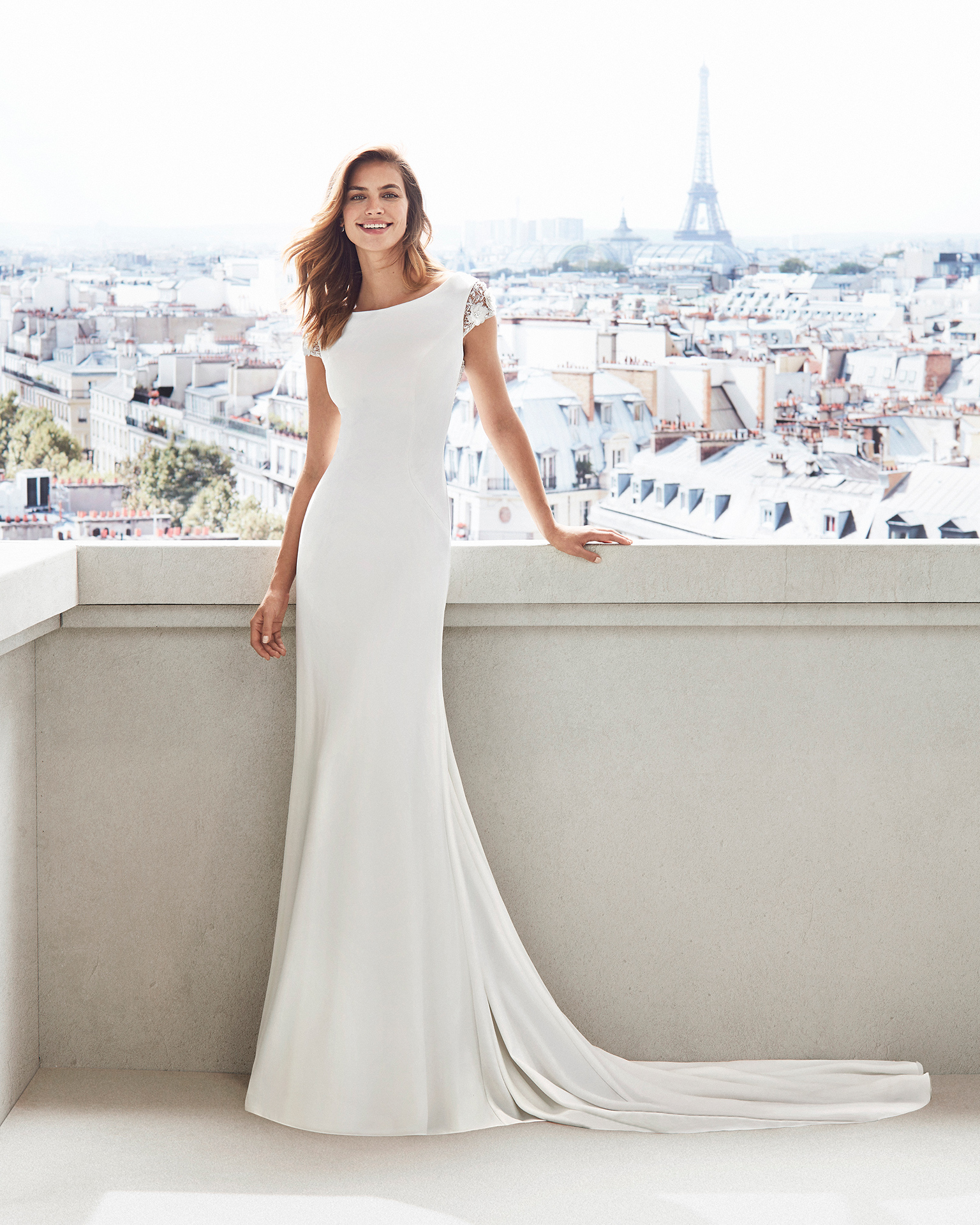 Sheath-style wedding dress in crepe. Bateau neckline, train and jewelled back. Available in natural. 2019  Collection.