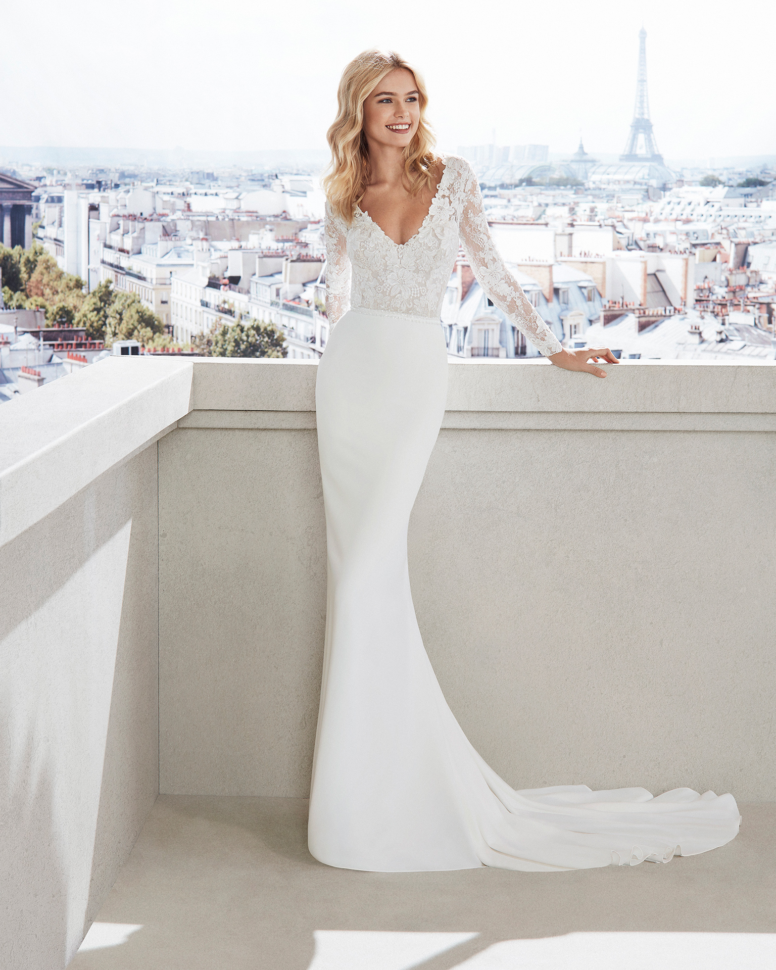 Sheath-style wedding dress in crepe. V-neck beaded belt,    lace bodice with long sleeves and train. Available in       natural. 2019  Collection.