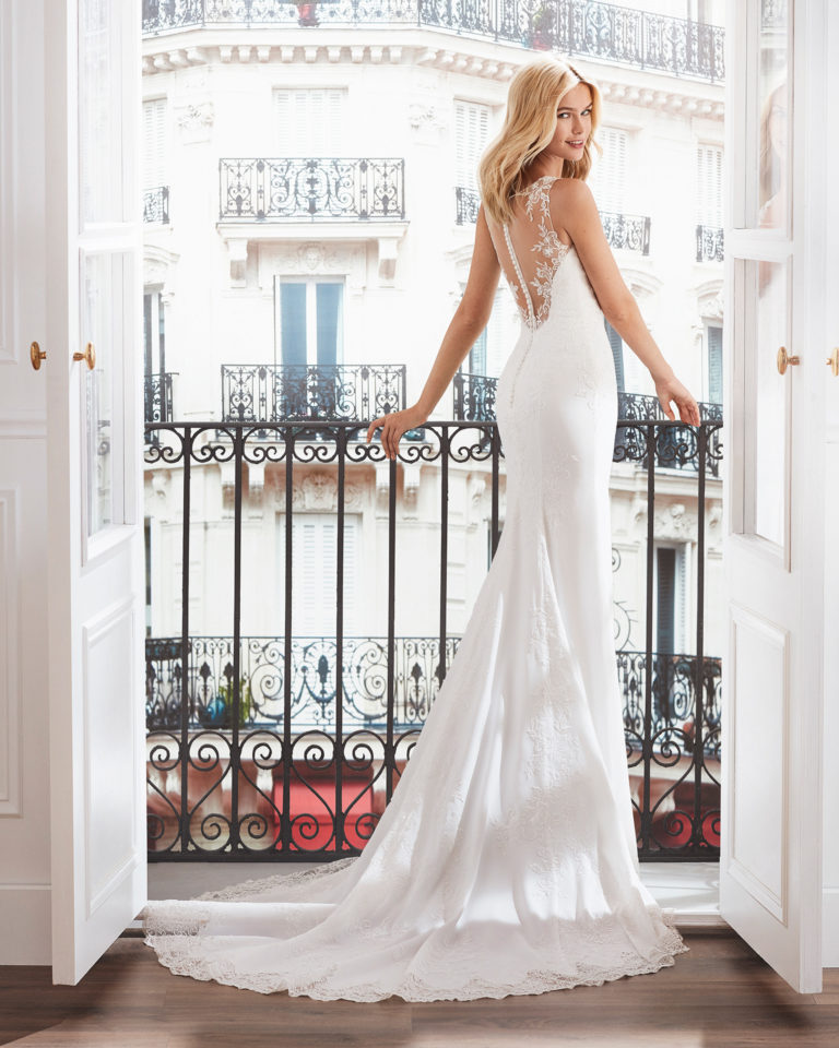 Sheath-style wedding dress in crepe. V-neck beaded lace bodice and train edged with lace. Available in natural. 2019  Collection.