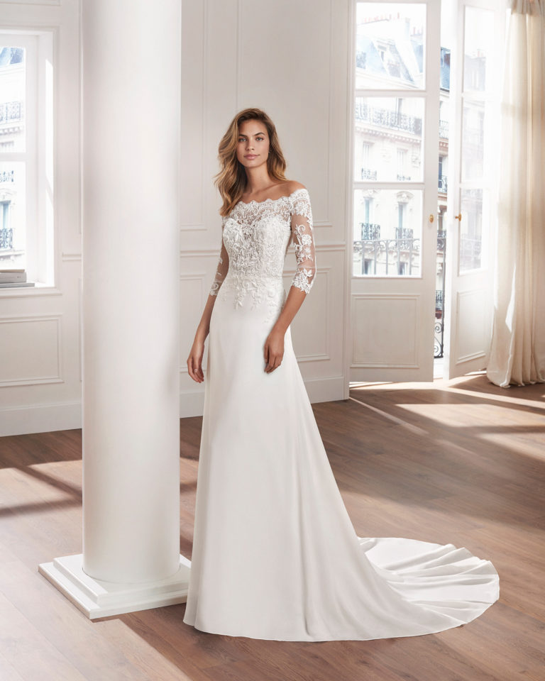 Sheath-style wedding dress in crepe Georgette. V-neck beaded lace bodice with long sleeves and train. Available in natural. 2019  Collection.