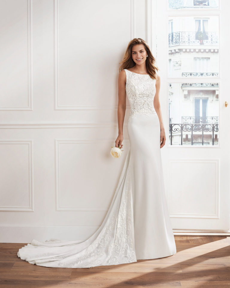 Sheath-style wedding dress in crepe Georgette. Beaded lace bodice with bateau neckline and train with beaded lace insets. Available in natural. 2019  Collection.