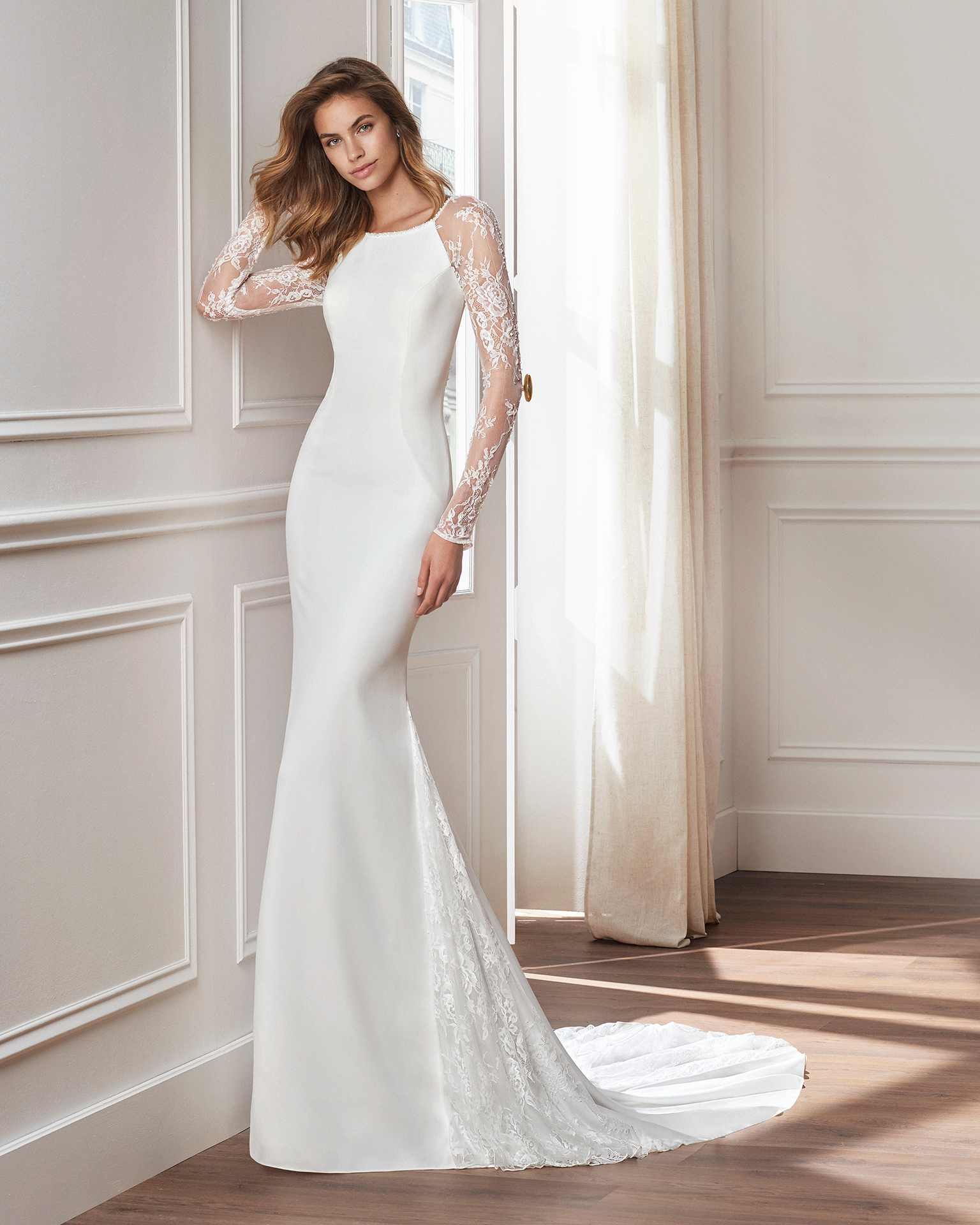 Sheath-style wedding dress in crepe. Long beaded lace sleeves and skirt with lace insets. Available in natural. 2019  Collection.