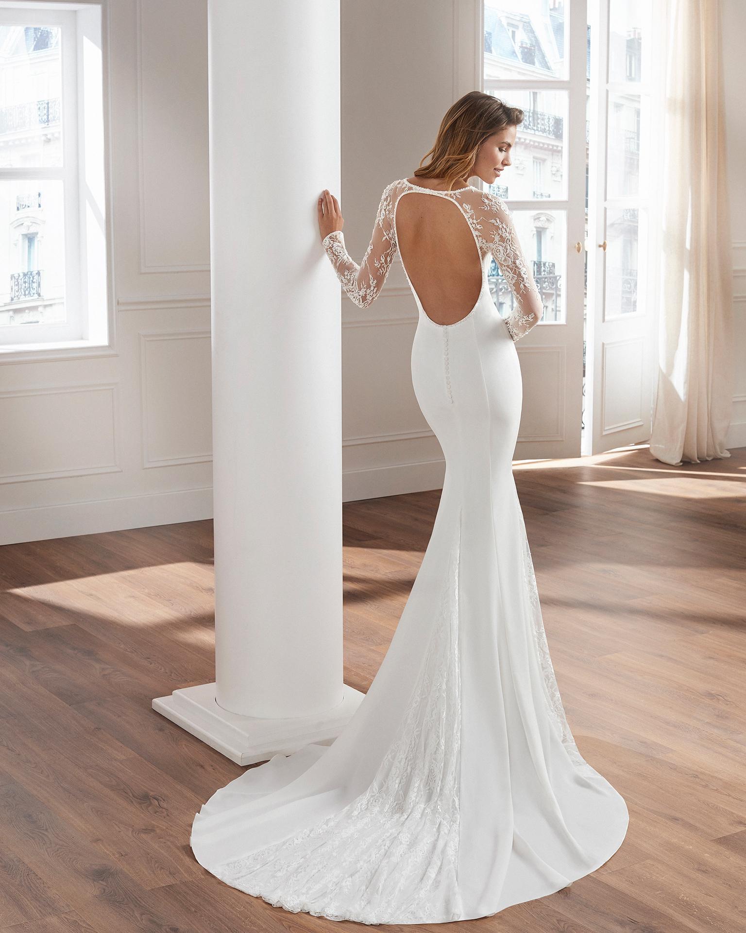 Vestido de novia corte recto en crepe. Manga larga de encaje con pedrería y encaje incrustado en la falda. Disponible en color natural. Colección  2019.
