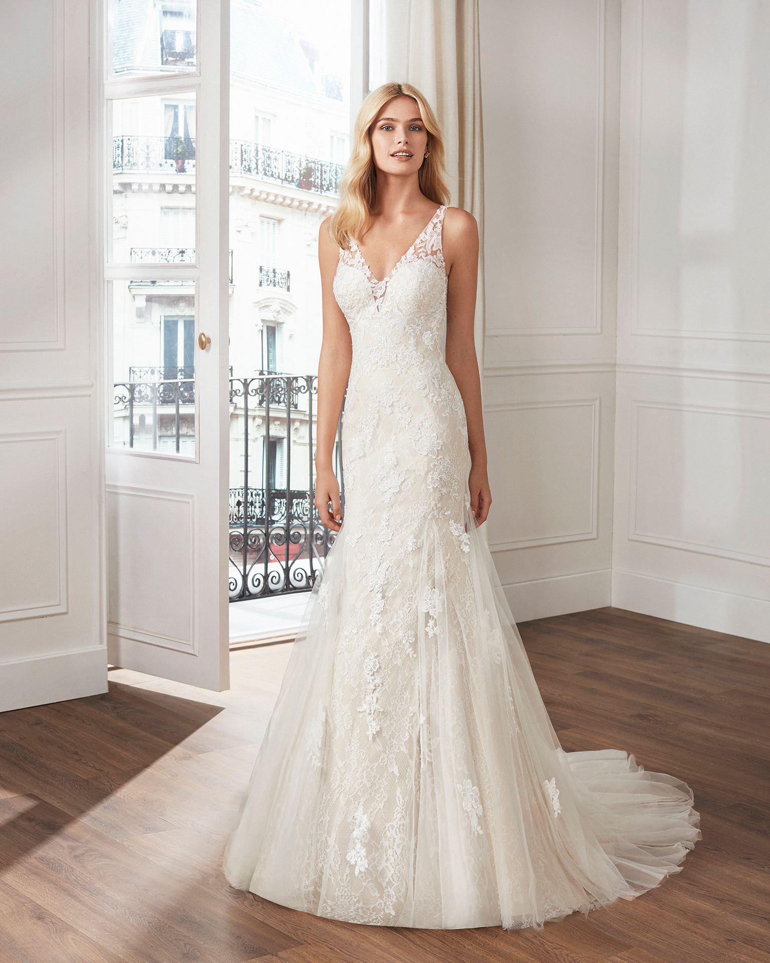 Mermaid-style wedding dress in beaded lace. V-neckline and teardrop back with appliquéd skirt. Available in natural and natural/champagne. 2019  Collection.