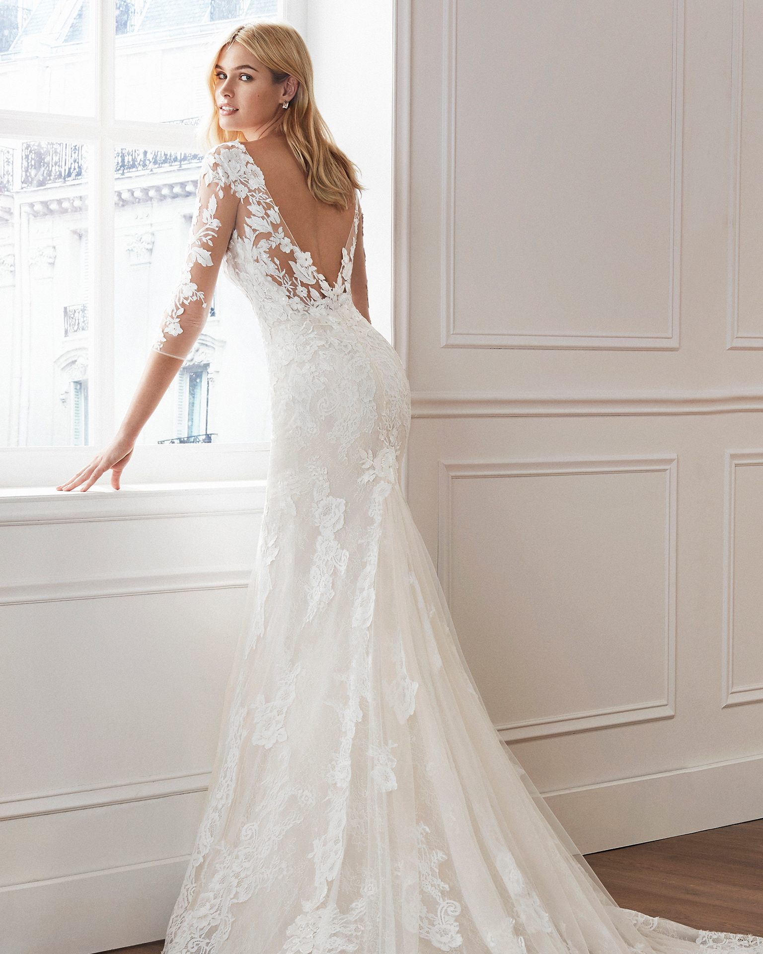 Mermaid-style wedding dress in beaded lace. Illusion neckline, long sleeves and appliquéd skirt. Available in natural and natural/nude. 2019  Collection.