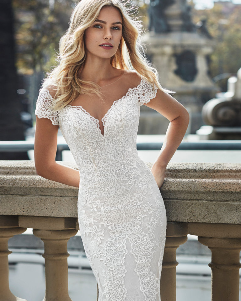 Mermaid-style wedding dress in beaded lace. Off-the-shoulder neckline, short sleeves and appliquéd skirt. Available in natural and natural/nude. 2019  Collection.