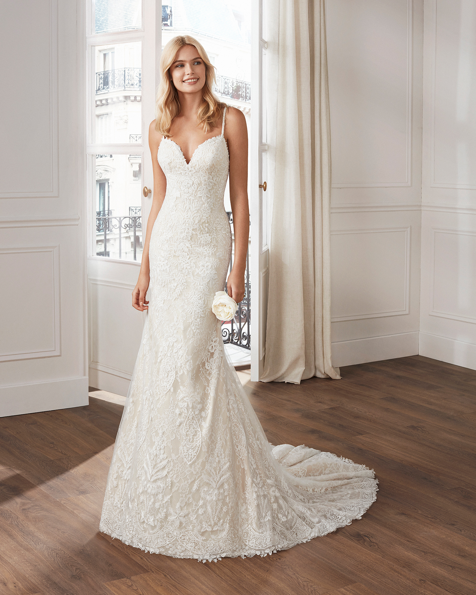 Mermaid-style lace wedding dress. V-neckline and appliquéd skirt, with beaded straps. Available in natural and          natural/champagne. 2019  Collection.