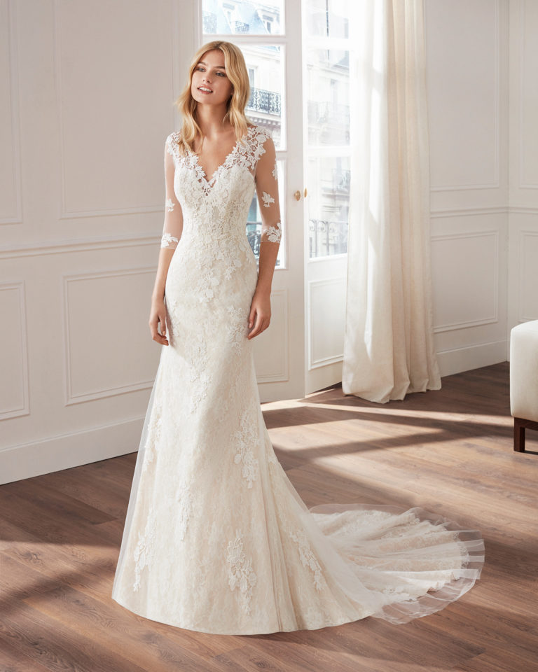 Mermaid-style lace wedding dress. V-neckline, long tulle sleeves and appliquéd skirt. Available in natural and natural/champagne. 2019  Collection.