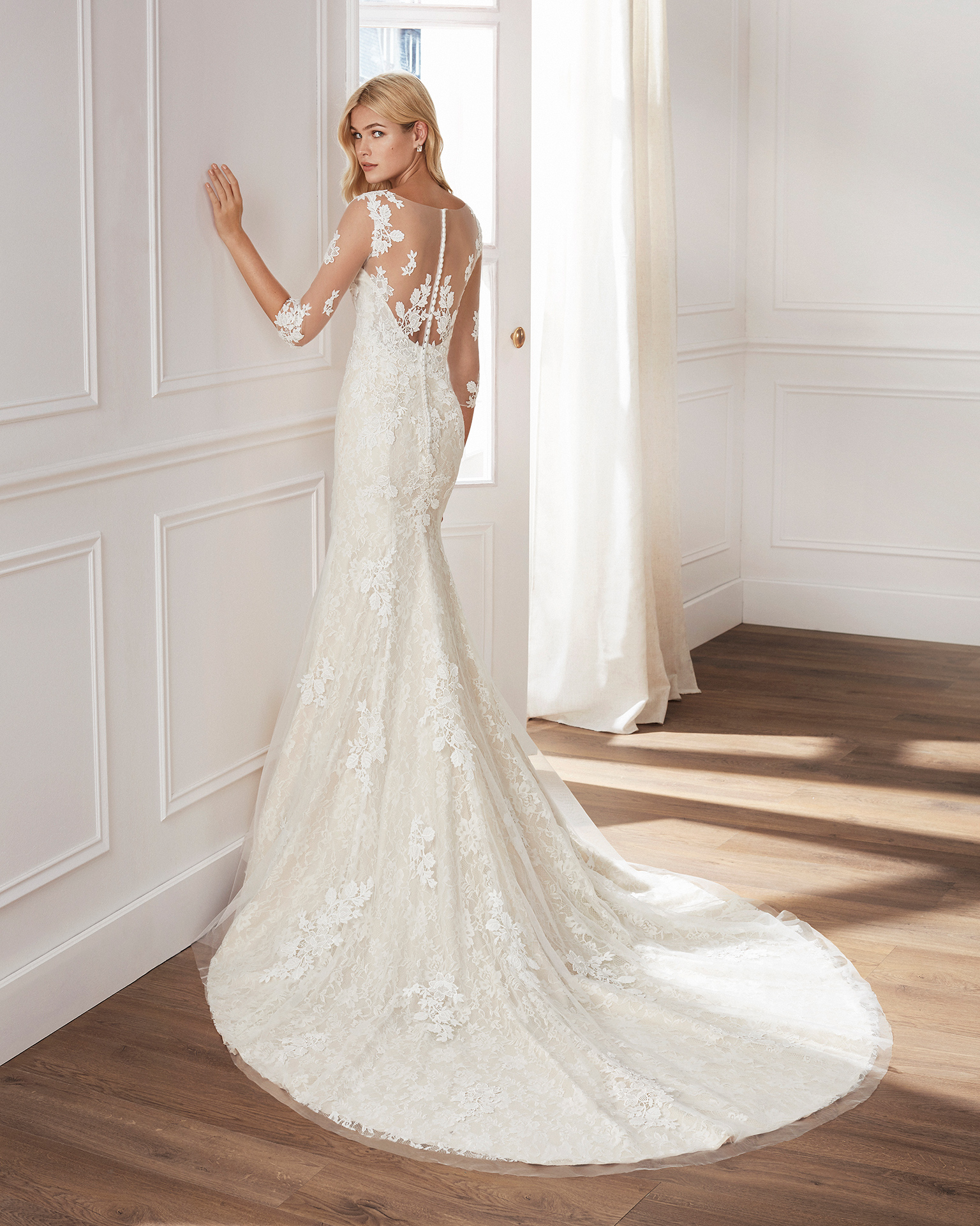 Vestido de novia corte sirena de encaje. Escote en V, manga larga de tul y falda de aplicaciones. Disponible en color natural y natural/champagne. Colección  2019.