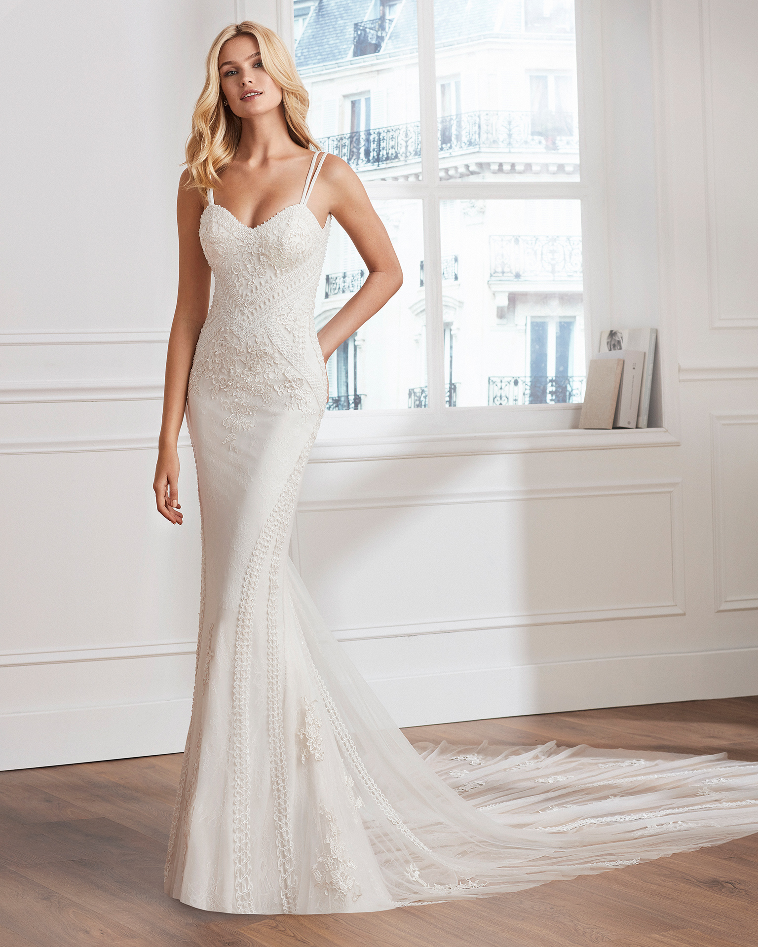 Sheath-style wedding dress in lace. Semi-sweetheart neckline and open back. Available in natural. 2019  Collection.