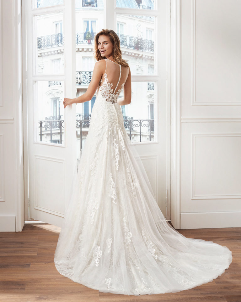 Sheath-style wedding dress in lace. V-neckline and appliquéd skirt. Available in ivory and natural. 2019  Collection.