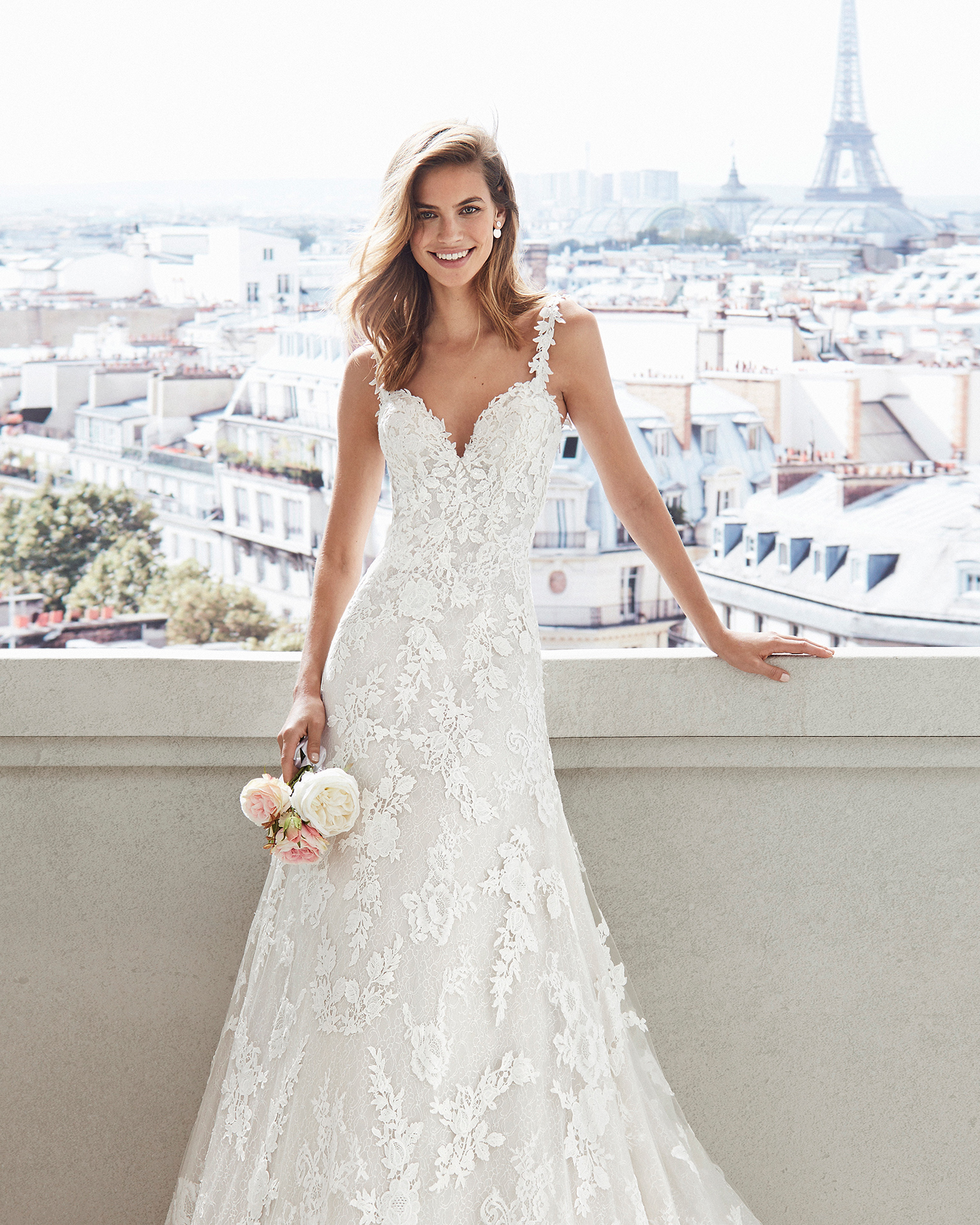Sheath-style wedding dress in lace. V-neckline and appliquéd skirt. Available in natural/nude and natural. 2019  Collection.