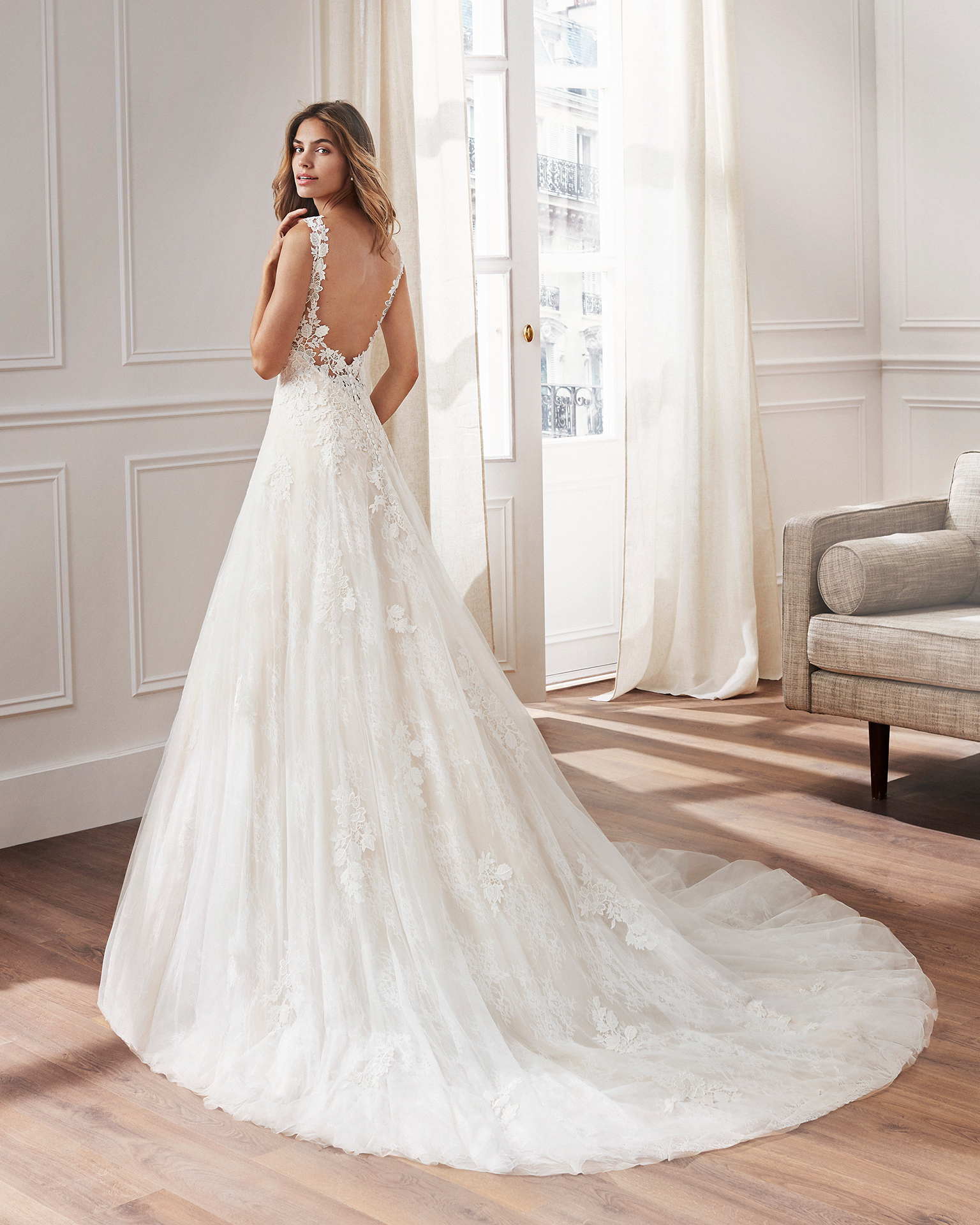 Ballgown-style wedding dress in lace. Sweetheart neckline, straps and appliquéd skirt. Available in natural and natural/nude. 2019  Collection.